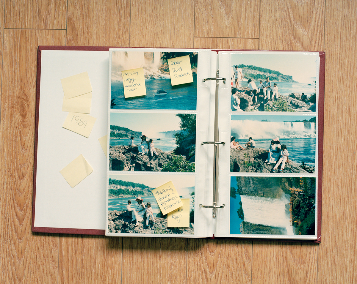 Family album covered in post-it notes, against a wood floor